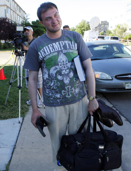 University of Colorado medical school researcher Dimitry Shchekochikhin, from Moscow, leaves after getting his computer and some clothes from his apartment in the same building of shooting suspect James Eagen Holmes in Aurora, Colo., Sunday, July 22, 2012. Shchekochikhin, 27, says he lived in the apartment house since November and had casual contact with Holmes. Holmes has been charged in the shooting at an Aurora theatre early Friday that killed twelve people and injured more than 50. (AP Photo/Ed Andrieski)