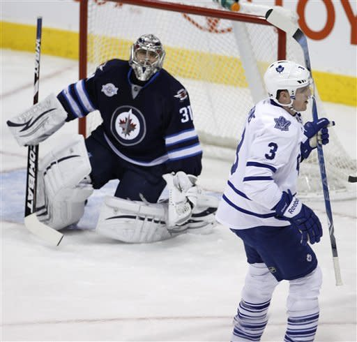 Toronto Maple Leafs' Dion Phaneuf (3) celebrates a goal by teammate Phil Kessel, not shown, on Winnipeg Jets goaltender Ondrej Pavelec in the first period of an NHL hockey game in Winnipeg, Manitoba, Tuesday, Feb. 7, 2012. (AP Photo/The Canadian Press, Trevor Hagan)