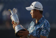 United States' Collin Morikawa looks at the claret jug trophy as he poses for photographers on the 18th green after winning the British Open Golf Championship at Royal St George's golf course Sandwich, England, Sunday, July 18, 2021. (AP Photo/Peter Morrison)