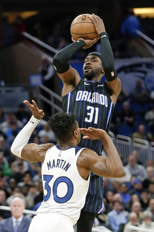 Orlando Magic guard Terrence Ross (31) makes a 3-point shot over Minnesota Timberwolves forward Kelan Martin (30) during the second half of an NBA basketball game Friday, Feb. 28, 2020, in Orlando, Fla. (AP Photo/John Raoux)