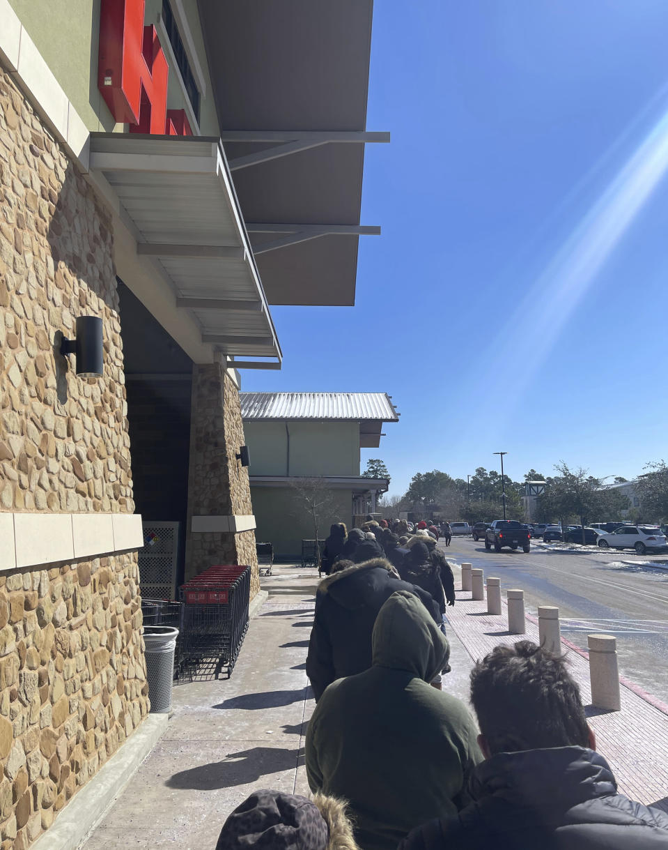 This photo provided by Rodney Giles people wait on line to enter a H-E-B grocery store on Tuesday, Feb. 17, 2021 near Woodlands, Texas. A series of winter storms and widespread power outages gripping Texas and other states not used to such extreme low temperatures are creating big challenges in the nation's food supply networks. (Rodney Giles via AP)
