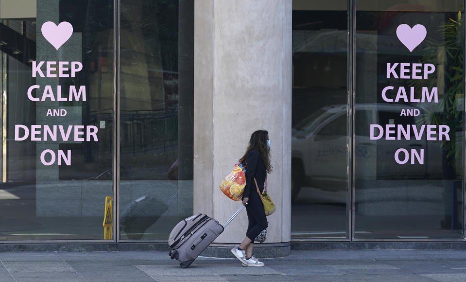 A lone traveler with luggage trudges toward a rental car location as the Memorial Day holiday weekend kicks into full swing early Friday, May 28, 2021, in downtown Denver. (AP Photo/David Zalubowski)