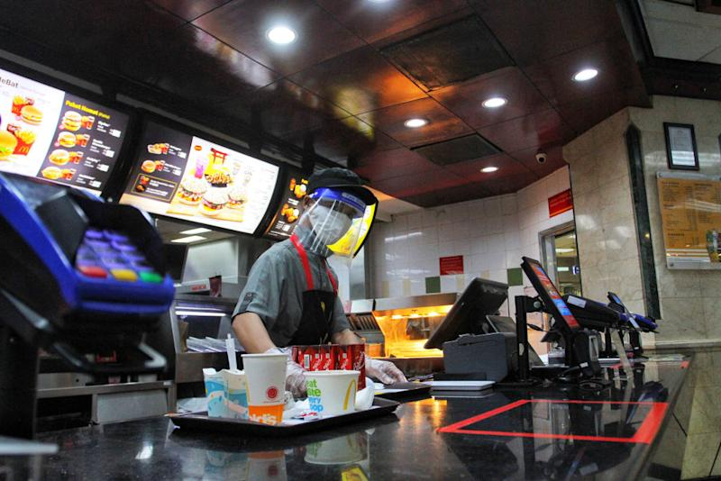 A Employee wears a face shield as he serve a order food at McDonald's restaurant in Indonesia. Source: Getty Images)