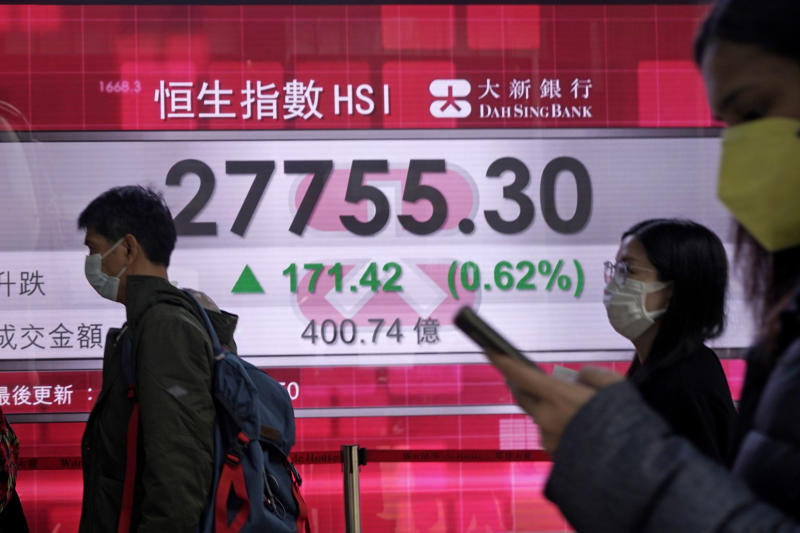 People walk past an electronic board showing Hong Kong share index outside a local bank in Hong Kong, Wednesday, Feb. 12, 2020. Asian shares were higher Wednesday, although the outbreak of a new virus in the region continued to weigh on investor sentiments. (AP Photo/Kin Cheung)