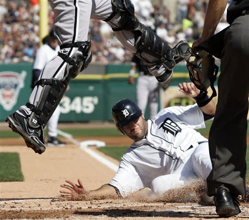 Detroit Tigers' Alex Avila, right, slides under Chicago White Sox catcher A.J. Pierzynski to score from second base on a single by Andy Dirks in the second inning of a baseball game, Saturday, May 5, 2012, in Detroit. (AP Photo/Duane Burleson)