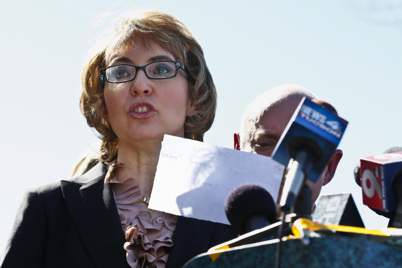 Giffords visits rampage site, urges gun control