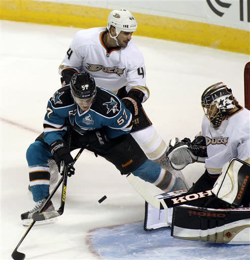 Anaheim Ducks goalie Jonas Hiller blocks a shot by San Jose Sharks' Tommy Wingels (57) as Ducks' Sheldon Souray watches during the first period of an NHL hockey game, Wednesday, March 27, 2013 in San Jose, Calif. (AP Photo/George Nikitin)