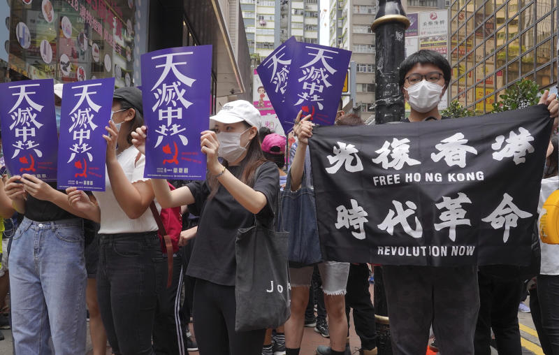 """Hundreds of protesters with banners march along a downtown street during a pro-democracy protest against Beijing's national security legislation in Hong Kong, Sunday, May 24, 2020. Hong Kong's pro-democracy camp has sharply criticised China's move to enact national security legislation in the semi-autonomous territory. They say it goes against the """"one country, two systems"""" framework that promises the city freedoms not found on the mainland. (AP Photo/Vincent Yu)"""