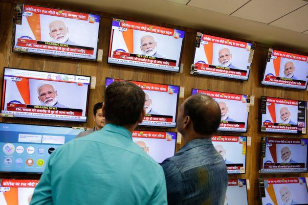 People watch Prime Minister Narendra Modi address the nation in a televised speech about COVID-19 situation, at an electronics store in Ahmedabad, March 19, 2020.