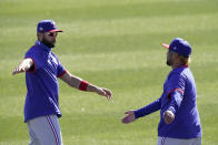 Texas Rangers' Isiah Kiner-Falefa, left, and Willie Calhoun stretch during spring training baseball practice Monday, Feb. 22, 2021, in Surprise, Ariz. (AP Photo/Charlie Riedel)