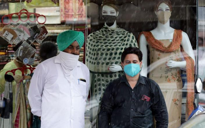 Indian men wearing face masks stand outside a shop with mannequins wearing face masks after new stricter guidelines issued by the state government in Amritsar - RAMINDER PAL SINGH/EPA-EFE/Shutterstock