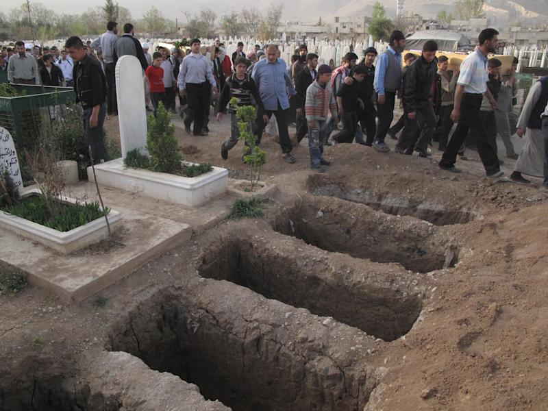 Mourners walk past open graves at a cemetery during the funeral for four people killed in a raid by government forces in a neighborhood of Damascus, Syria, Thursday, April 5, 2012. Syrian troops launched a fierce assault Thursday, days ahead of a deadline for a U.N.-brokered cease-fire, with activists describing it as one of the most violent attacks around the capital since the year-old uprising began.(AP Photo)