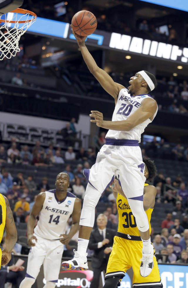 Kansas State's Xavier Sneed (20) drives past UMBC's Daniel Akin (30) during the second half of a second-round game in the NCAA men's college basketball tournament in Charlotte, N.C., Sunday, March 18, 2018. (AP Photo/Bob Leverone)