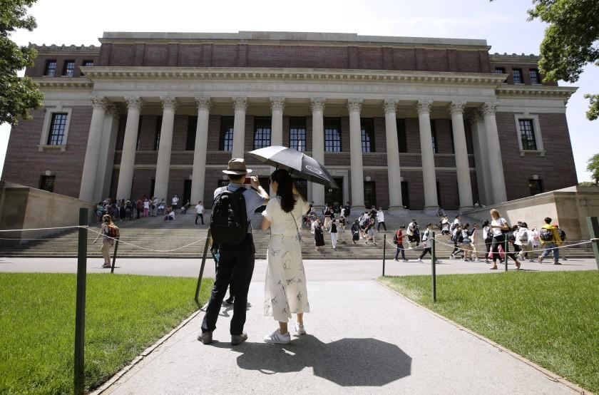 FILE - In this July 16, 2019, file photo, people stop to record images of Widener Library on the campus of Harvard University in Cambridge, Mass. U.S. District Judge Allison D. Burroughs ruled, Tuesday, Oct. 1, 2019, that Harvard does not discriminate against Asian Americans in its admissions process. The judge issued the ruling in a 2014 lawsuit that alleged Harvard holds Asian American applicants to a higher standard than students of other races. Burroughs said Harvard's admissions process is not perfect but passes constitutional muster. (AP Photo/Steven Senne, File)