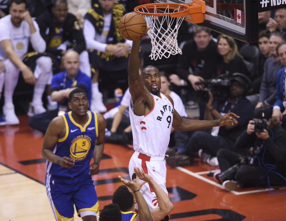 Toronto Raptors centre Serge Ibaka (9) rebounds the ball near Golden State Warriors centre Kevon Looney (5) during the first half of Game 1 of basketball's NBA Finals, Thursday, May 30, 2019, in Toronto. (Nathan Denette/The Canadian Press via AP)