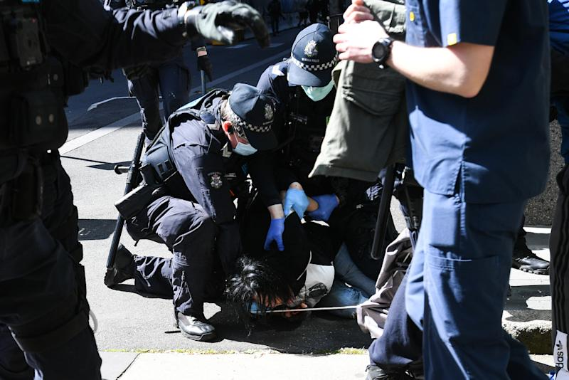 Picture of police arresting a protester at an anti-lockdown rally in Melbourne