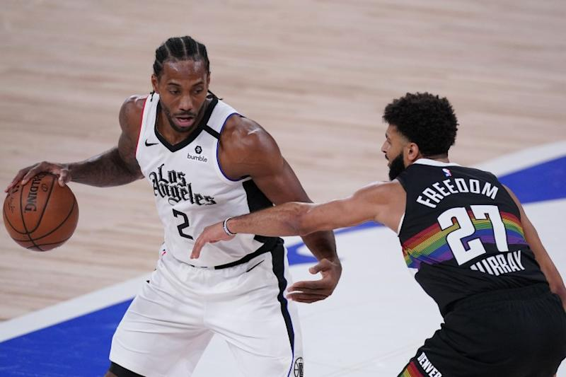 Los Angeles Clippers' Kawhi Leonard (2) tries to get past Denver Nuggets' Jamal Murray (27) during the first half of an NBA conference semifinal playoff basketball game Monday, Sept. 7, 2020, in Lake Buena Vista, Fla. (AP Photo/Mark J. Terrill)