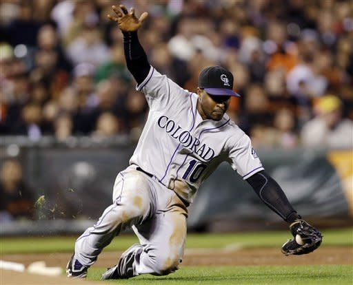 Colorado Rockies third baseman Chris Nelson makes a sliding play on a ground ball from San Francisco Giants' Tim Lincecum during the fourth inning of a baseball game, Tuesday, Sept. 18, 2012, in San Francisco. Nelson threw out Lincecum at first base. (AP Photo/Marcio Jose Sanchez)