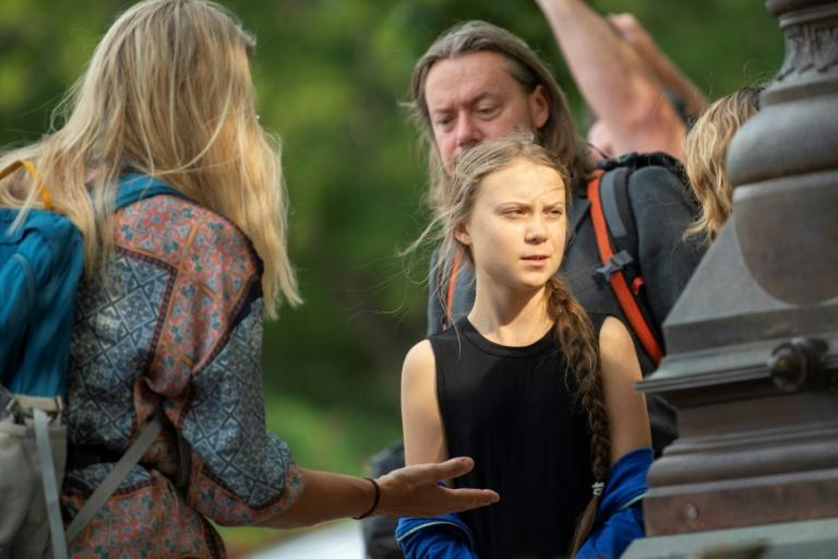 Swedish environmental activist Greta Thunberg (C) talks with members of her close entourage as she takes part in a media event on Capitol Hill on September 17, 2019 in Washington