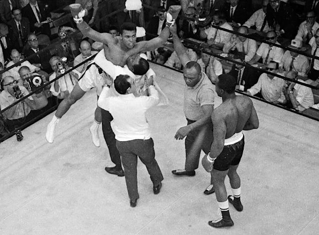 FILE - In this May 25, 1965, file photo, heavyweight champion Muhammad Ali is lifted by happy handlers as referee Joe Walcott steps between them and challenger Sonny Liston after Liston was knocked out in the first round of their title fight in Lewiston, Maine. The bout produced one of the strangest finishes in boxing history as well as one of sports' most iconic moments. (AP Photo/File)