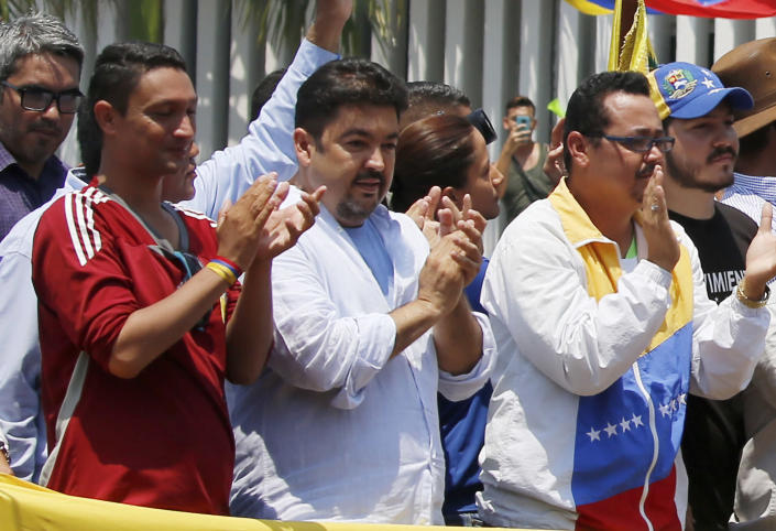In this Saturday, March 16, 2019 photo, lawyer Roberto Marrero, center, applauds upon his arrival to a rally of Venezuelan opposition leader Juan Guaido, who has declared himself interim president in Valencia, Venezuela. Venezuelan security forces detained Marrero, a key aide to opposition leader Juan Guaido in a raid on his home early Thursday, March 21 an opposition lawmaker said. Marrero was taken by intelligence agents in the overnight operation in Caracas. (AP Photo/Fernando Llano)