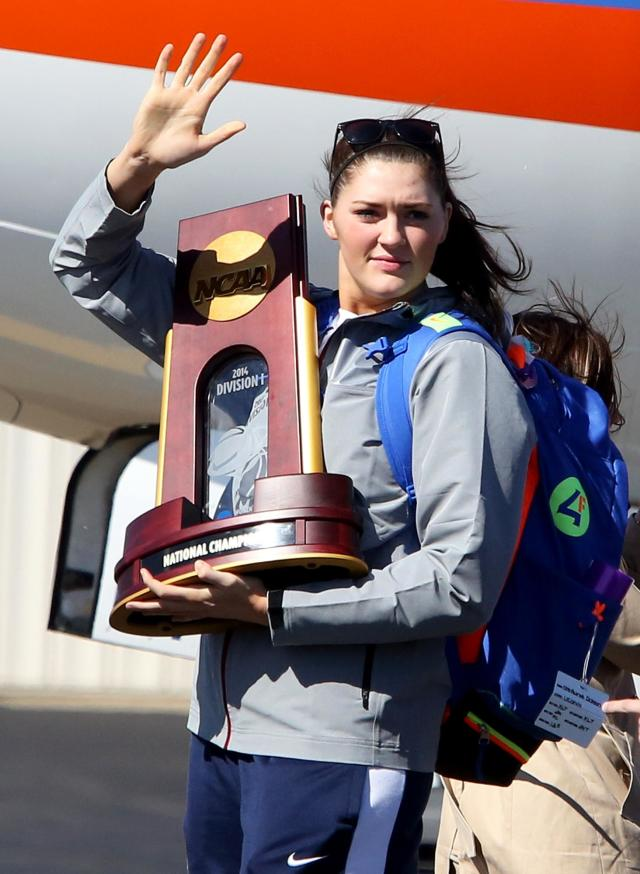 Connecticut's Stephanie Dolson waves to fans while carrying the NCAA National Championship Trophy at Bradley International Airport in Windsor Locks, Conn., Wednesday, April 9, 2014, the day after the Huskies defeated Notre Dame to clinch their ninth national championship. (AP Photo/Journal Inquirer, Jared Ramsdell)