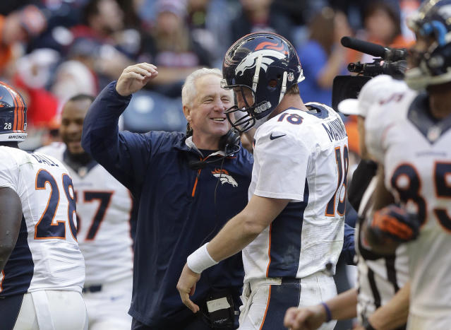 Denver Broncos coach John Fox, left, celebrates with Peyton Manning (18) after Manning threw a touchdown pass during the fourth quarter of an NFL football game against the Houston Texans, Sunday, Dec. 22, 2013, in Houston. (AP Photo/Patric Schneider)