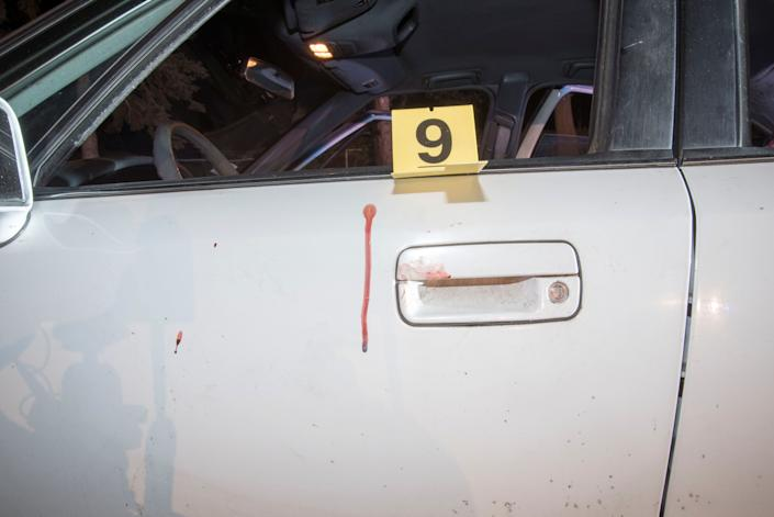 Bloodstains and a marker are seen on the car.