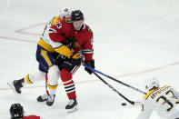 Nashville Predators' Mattias Ekholm, left, checks Chicago Blackhawks' Philipp Kurashev (23) off the puck during the third period of an NHL hockey game Wednesday, April 21, 2021, in Chicago. (AP Photo/Charles Rex Arbogast)