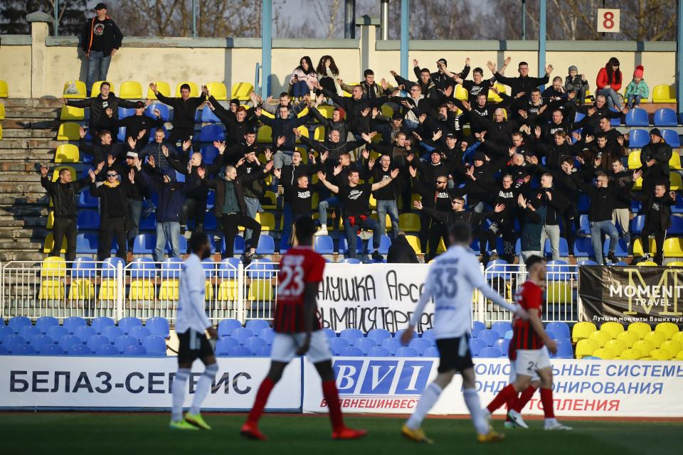 In this photo taken on Friday, March 27, 2020, fans of Torpedo Zhodino cheer during the Belarus Championship soccer match between Torpedo-BelAZ Zhodino and Belshina Bobruisk in the town of Zhodino, Belarus. Longtime Belarus President Alexander Lukashenko is proudly keeping soccer and hockey arenas open even though most sports around the world have shut down because of the coronavirus pandemic. The new coronavirus causes mild or moderate symptoms for most people, but for some, especially older adults and people with existing health problems, it can cause more severe illness or death. (AP Photo/Sergei Grits)