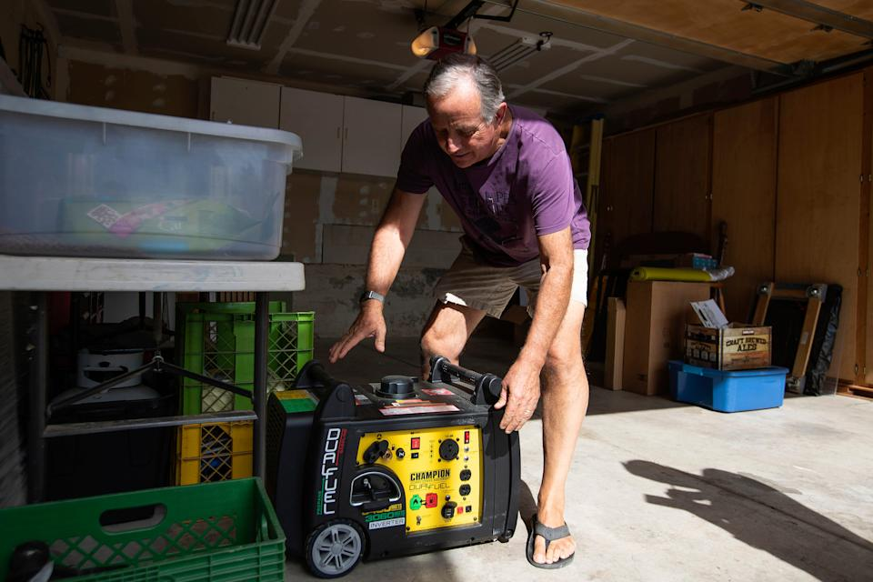 Joe Wilson pulls his generator out in the garage of his home, which is in an area that is expected to lose power early Wednesday, in the East Foothills area of San Jose, Calif., Oct. 8, 2019.