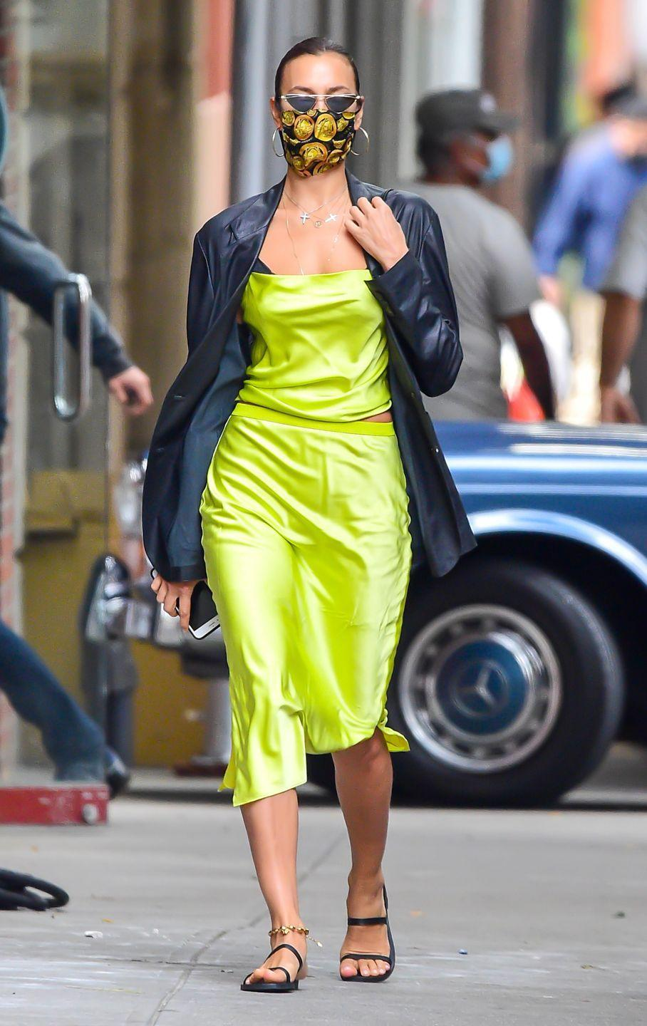 <p>The model was seen wearing a lime green slip dress and a black, leather coat while on the school run in New York City on October 19.</p><p>The 34-year-old model teamed her look with a pair of gold hoop earrings, black sandals and a gold and lime green-coloured black face mask.</p>