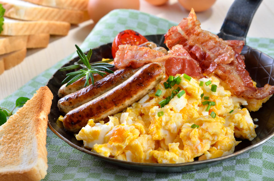 Scrambled eggs with fried bacon and sausages served in a pan with toast