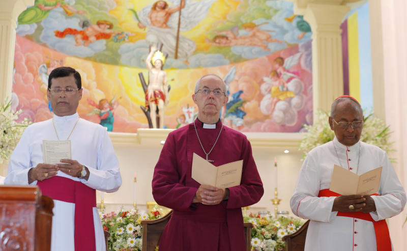 The Archbishop of Canterbury Justin Welby, center, pays homage to victims of the Easter Sunday attacks at St. Sebastian's church in Katuwapitiya village, Negombo , Sri Lanka, Thursday, Aug. 29, 2019. The figurehead of the Church of England emphasized the need for Christian unity on Thursday as he paid tribute to the victims of the Easter Sunday bomb attacks at a Roman Catholic church in Sri Lanka. A total of 263 people were killed when seven suicide bombers from a local Muslim group attacked three churches and three luxury hotels on April 21. (AP Photo/Eranga Jayawardena)