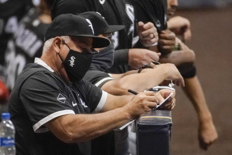 Chicago White Sox manager Rick Renteria takes notes during the seventh inning of a baseball game against the Milwaukee Brewers Monday, Aug. 3, 2020, in Milwaukee. (AP Photo/Morry Gash)