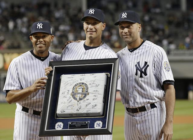 New York Yankees relief pitcher Mariano Rivera, left, and shortstop Derek Jeter, right, present pitcher Andy Pettitte, center, with a base from his final game, before the Yankees' baseball game against the Tampa Bay Rays, Wednesday, Sept. 25, 2013, in New York. (AP Photo/Kathy Willens)
