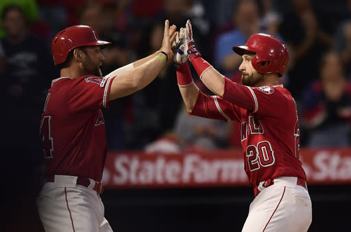 Los Angeles Angels' Jonathan Lucroy, right, is congratulated by Kevan Smith after hitting a two-run home run during the second inning of a baseball game against the New York Yankees, Monday, April 22, 2019, in Anaheim, Calif. (AP Photo/Mark J. Terrill)