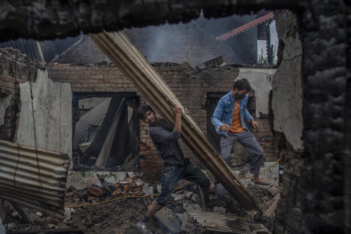 A Kashmiri villager carries corrugated tin sheet as he clears the house destroyed in a gunfight in Pulwama, south of Srinagar, Indian controlled Kashmir, Wednesday, July 14, 2021. Three suspected rebels were killed in a gunfight in Indian-controlled Kashmir on Wednesday, officials said, as violence in the disputed region increased in recent weeks. Two residential houses were also destroyed. (AP Photo/ Dar Yasin)