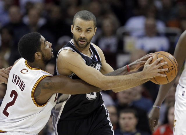 Cleveland Cavaliers' Kyrie Irving (2) tries to poke the ball away from San Antonio Spurs' Tony Parker during the second quarter of an NBA basketball game Tuesday, March 4, 2014, in Cleveland. (AP Photo/Mark Duncan)