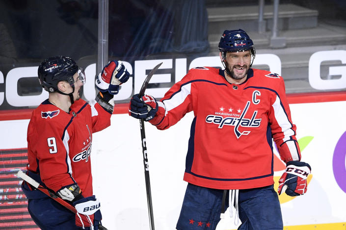 Washington Capitals left wing Alex Ovechkin, right, celebrates his goal with defenseman Dmitry Orlov (9) during the second period of an NHL hockey game against the New York Rangers, Sunday, March 28, 2021, in Washington. (AP Photo/Nick Wass)
