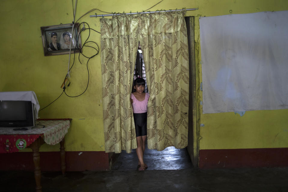 Nine-year-old Adriana Wong looks out from between curtains serving as a room divider inside her home where she lived with her father Herman Wong, who died from complications due to COVID-19, on the outskirts of Iquitos, Peru, Sunday, March 21, 2021. Herman Wong, a camera repairman died in the arms of his wife in April 2020 as he waited to be received at the hospital that was was full of people and short of beds. (AP Photo/Rodrigo Abd)