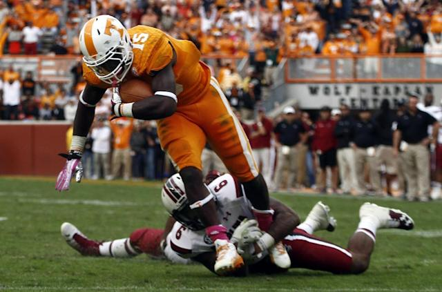 Tennessee running back Marlin Lane (15) leans for yardage after a catch as he's tackled by South Carolina safety Chris Moody (6) in the fourth quarter of an NCAA college football game on Saturday, Oct. 19, 2013 in Knoxville, Tenn. The play set up the game-winning field goal by Michael Palary to give Tennessee a 23-21 victory. (AP Photo/Wade Payne)