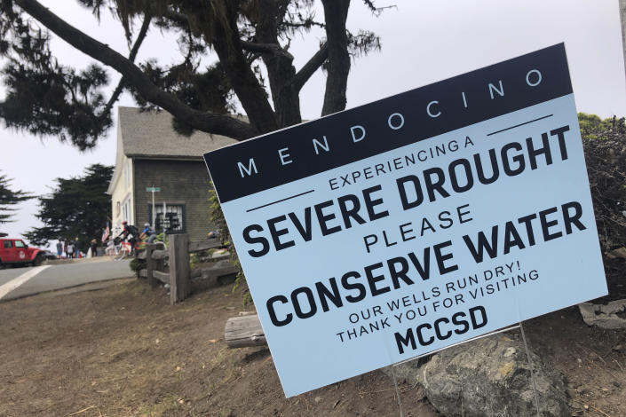 """Signs alert visitors to the severe drought in Mendocino, Calif., on Wednesday, Aug. 4, 2021. Tourists flock to the picturesque coastal town of Mendocino for its Victorian homes and cliff trails, but visitors this summer will also find public portable toilets and dozens of signs on picket fences announcing the quaint Northern California hamlet: """"Severe Drought Please conserve water."""" (AP Photo/Haven Daley)"""