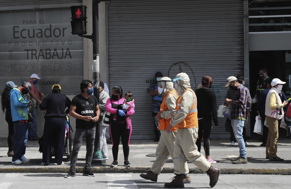 Workers dressed in protective from head to toe walk past pedestrians wearing protective face masks as a mandatory measure to help curb the spread of the new coronavirus, walk past in downtown Quito, Ecuador, Wednesday, June 10, 2020. The city is returning to a new normality after relaxing a rigorous quarantine but amid a certain fear that COVID-19 infections may rise. (AP Photo/Dolores Ochoa)