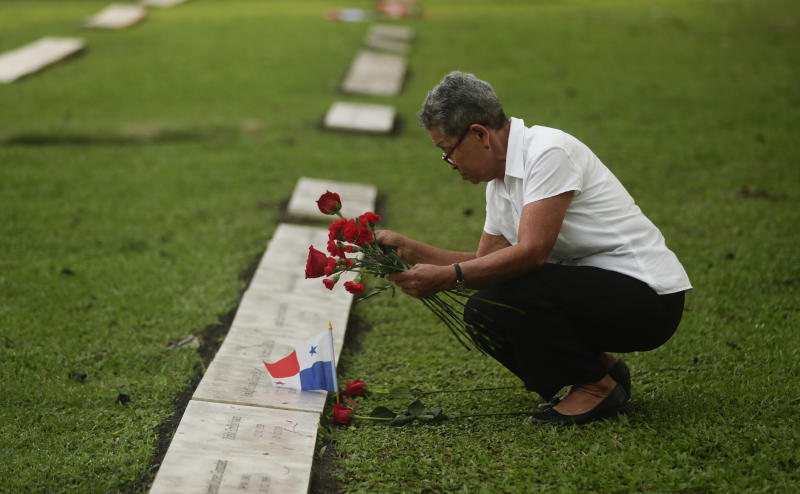 A woman places flowers on the grave of a person who died during the 1989 U.S. military invasion that ousted Panamanian strongman Manuel Noriega, on the 30th anniversary of the invasion in Panama City, Friday, Dec. 20, 2019. According to official figures, 300 Panamanian soldiers and 214 civilians died during the invasion, though the number remains controversial and human rights groups believe it is much higher. Twenty-three U.S. soldiers also perished. (AP Photo/Arnulfo Franco)
