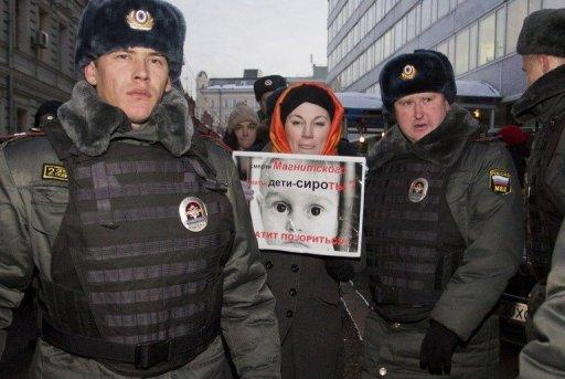 <p>A woman at Moscow's State Duma with a poster saying: 'Are orphans guilty of Sergei Magnitsky's death?' Magnitsky died in horrible pain at only 37 while he was under arrest over a fraud probe.</p>
