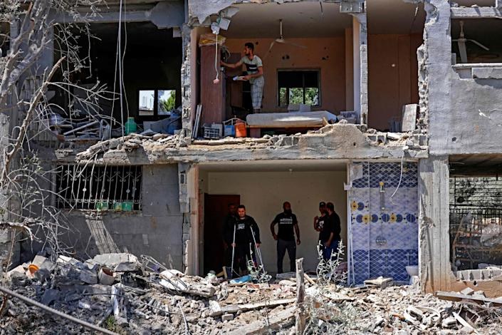 Palestinians assess the damage in a building caused by Israeli air strikes, in Beit Hanun in the northern Gaza Strip, on May 14, 2021.