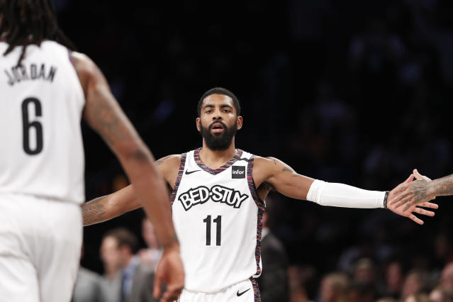 Brooklyn Nets guard Kyrie Irving (11) slaps hands with his teammates, including DeAndre Jordan (6), during the first half of an NBA basketball game against the Atlanta Hawks, Sunday, Jan. 12, 2020, in New York. (AP Photo/Kathy Willens)
