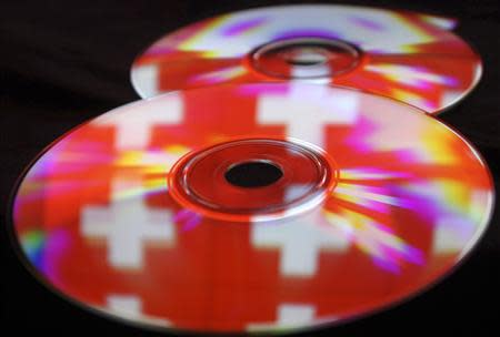 Compact discs with images of the Swiss flag are seen in this photo illustration taken in the central Bosnian town of Zenica, May 3, 2013. REUTERS/Dado Ruvic
