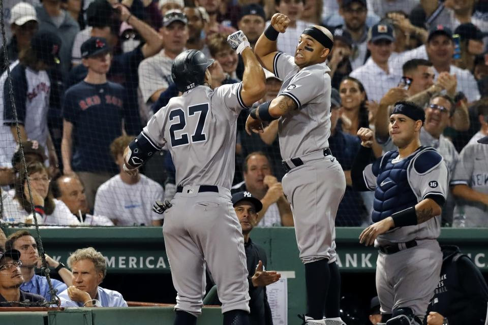 New York Yankees' Giancarlo Stanton (27) celebrates his grand slam with Rougned Odor, center, during the eighth inning of a baseball game against the Boston Red Sox, Saturday, Sept. 25, 2021, in Boston. (AP Photo/Michael Dwyer)